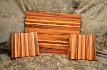 "# 13-03. Velda's cutting board and cheese board set. Goncalo Alves, Jatoba, Black Walnut, Cherry and Honey Locust. Cutting Board is 16"" x 22"" x 1-1/4"". Cheese boards are 9"" x 11"" x 1""."